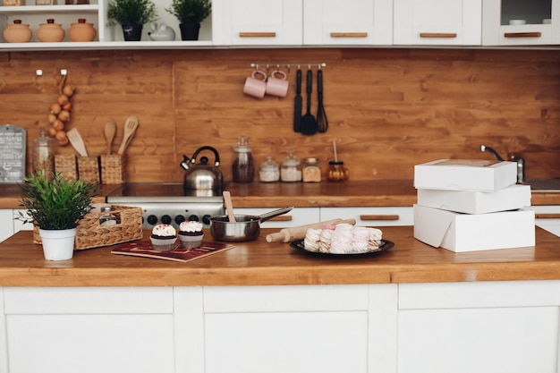 Picture of cupcakes, marshmellows, white boxes with sweets on the cupboard