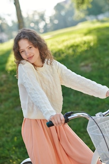 A picture of a cute girl on a bike in the park