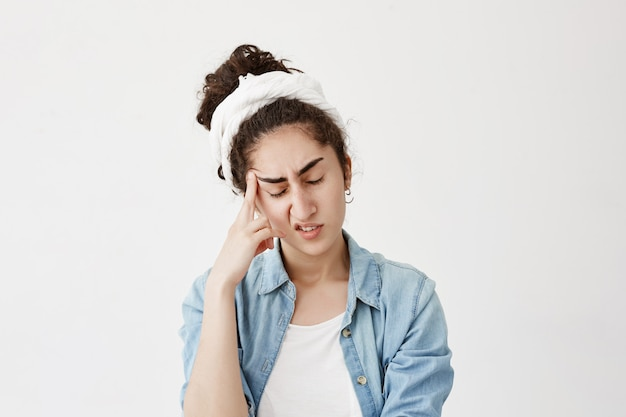 Picture of dark-haired pensive female model in white do-rag with closed eyes keeps hand on temple, suffers from headache after being worried, feels badly. negative emotions and face expression.