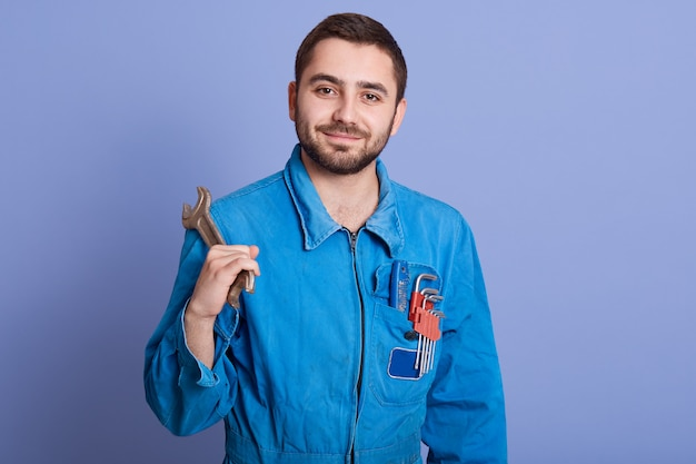 Picture of delighted hard working construction worker looking directly at camera, standing isolated over lilac background in studio, holding wrench in one hand. people and workplace concept.