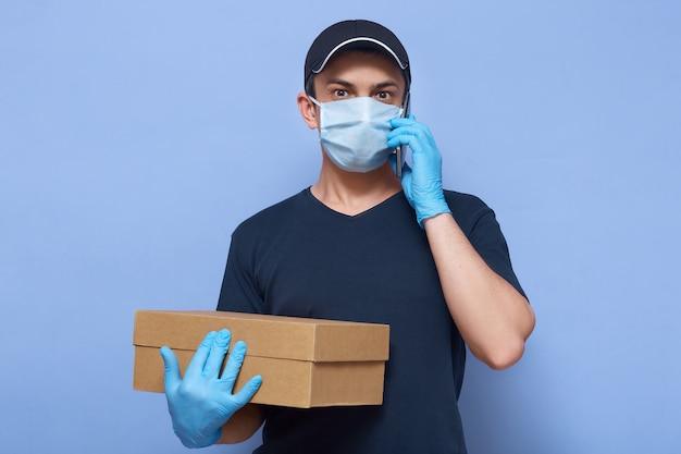 Picture of delivery man employee wearing cap, t shirt, mask and gloves, holds brown carton box, looks astonished, talks via phone against blue wall.