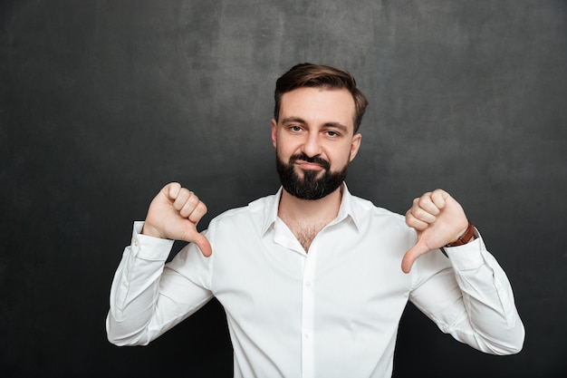 Picture of disappointed guy 30s gesturing on camera with thumbs down over dark gray