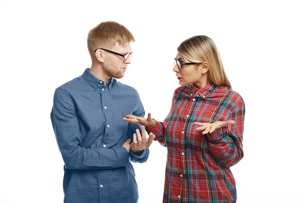 Picture of displeased frustrated young bearded male manager expressing indignation while having disagreement with his blonde female colleague over something. people, relationships and argument