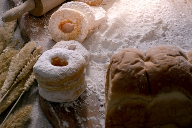 Picture of doughnuts with icing sugar on wooden table, food concept.