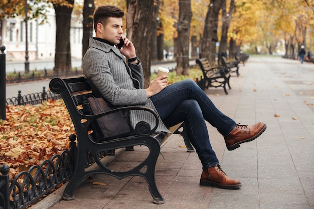 Picture of elegant brunette male in coat and jeans drinking takeaway coffee and talking on smartphone, while sitting on bench in park