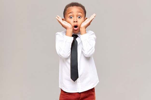 Picture of emotional funny surprised african american schoolboy in shirt and tie holding hands at his face, widening eyes and opening mouth widely, being shocked with astonishing unexpected news