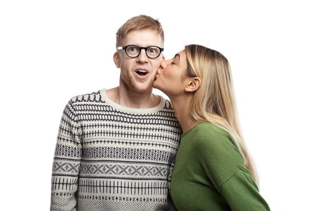 Immagine di giovane nerd divertente emotivo che indossa occhiali rettangolari esclamando eccitato, aprendo la bocca ampiamente come ragazza attraente che lo bacia sulla guancia. persone, amore, romanticismo e appuntamenti