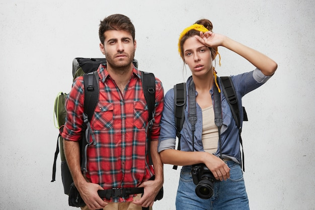 Picture of exhausted frustrated guy and woman of european appearance carrying rucksacks on their shoulders feeling tired and worn out after spending sleepless night on the road while hitchhiking
