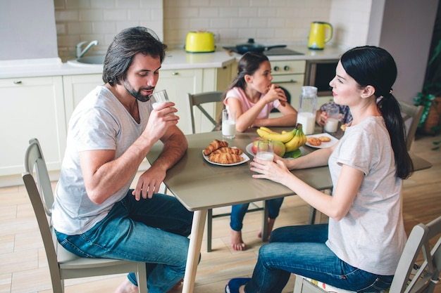 A picture of family sitting at table. parents are sitting in front of kids. man drinks milk. woman looks at him. kids are eating and talking with each other.