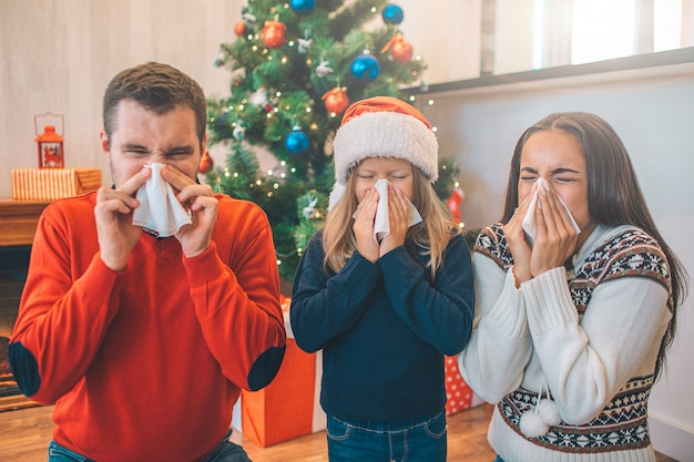 Picture of family suffering from sickness. they blow their noses using napkins.