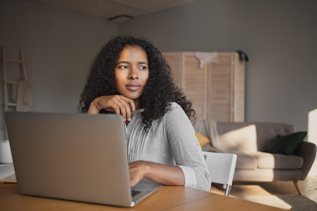 Picture of fashionable attractive young dark skinned woman freelancer in shirt sitting at workplace at home and using high speed wirless internet connection on laptop, having thoughtful look