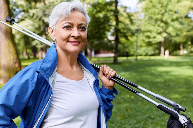 Picture of fashionable confident european lady with gray short hair standing in pine forest with nordic walking sticks on shoulders, going home after cardio workout, smiling broadly