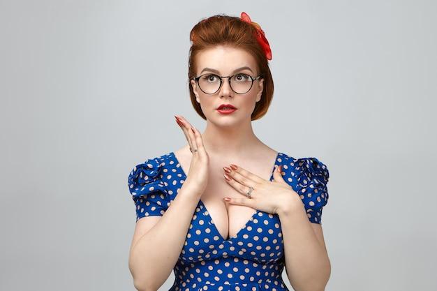 Foto di giovane donna affascinante alla moda che indossa un abito elegante, acconciatura vintage e occhiali alla moda guardando in alto, tenendo la mano sul petto, avendo preoccupato l'espressione facciale frustrata