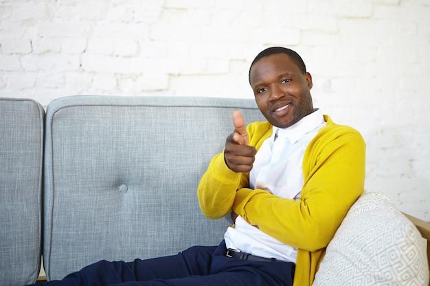 Foto di giovane maschio africano gioioso alla moda che indossa jeans, cardigan giallo e camicia bianca rilassante nel soggiorno, comodamente seduto sul divano grigio, sorridente e puntando il dito indice alla telecamera