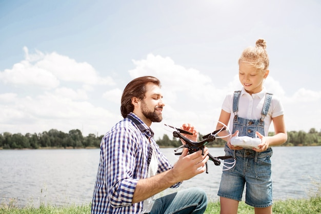 A picture of father and daughter spending time together. guy is holding drone and showing it to girl while small kid has control panel in her hands. child is looking at drone as well.