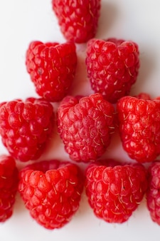A picture of a few fresh pink raspberries lies on a white background. background and picture for postcard.