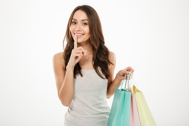 Picture of flirting woman holding shopping packs and asking keep secret with putting finger on lips, isolated over white wall