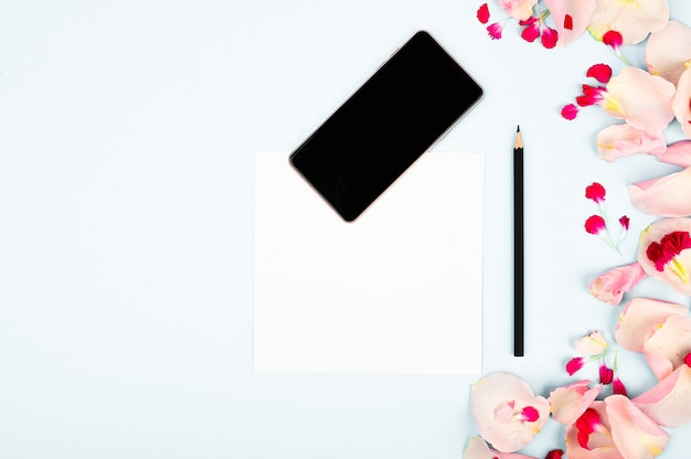 レディースブログの画像です。花、ノート、スマートフォン、紙の背景に鉛筆でフラットレイアウト