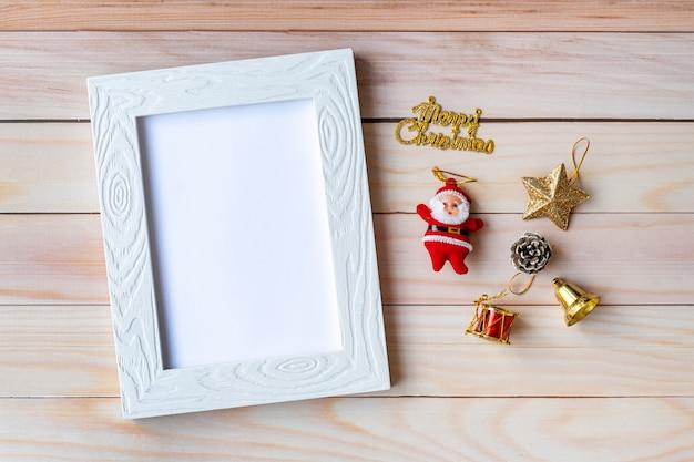 Картинная рамка и рождественские украшения - санта-клаус и подарок на деревянном столе. рождество и новый год концепция