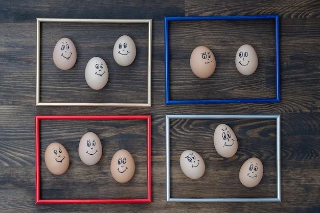 사진 프레임과 어두운 나무 벽 배경에 웃고 있는 많은 재미있는 계란이 닫힙니다. 계란 가족 감정 얼굴 초상화입니다. 개념 재미있는 음식 프리미엄 사진