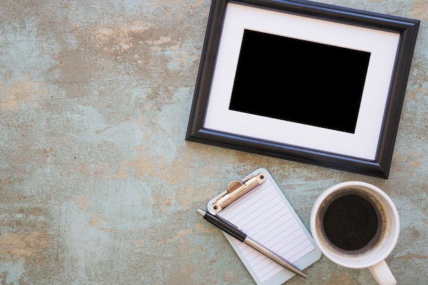 Picture frame; coffee cup with clipboard and pen on rustic background