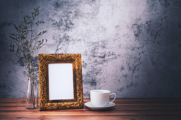 Picture frame and flowers and coffee mugs on wooden table