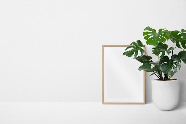 Cornice per foto appoggiata a un muro bianco