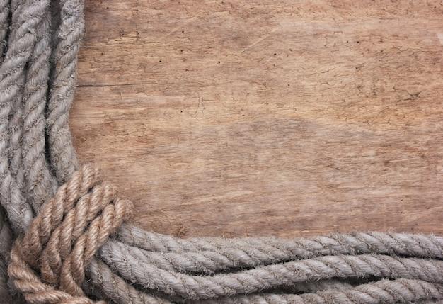 古い木製の背景にロープの額縁