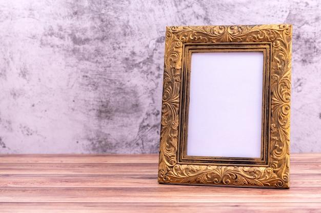 Картинная рамка на стене и деревянном столе.