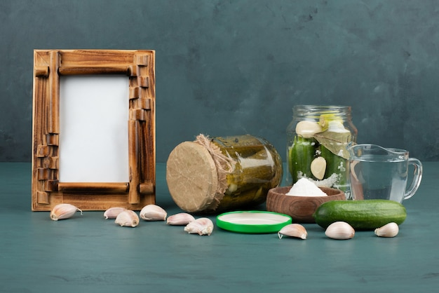Picture frame, pickled vegetables in glass jar and salt bowl on blue surface with fresh cucumber and garlic.