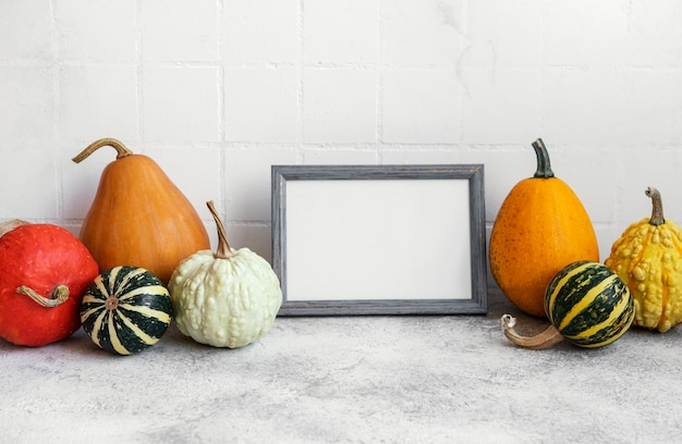 Picture frame and pumpkin decor on the table over white tile background. fall season greeting card.