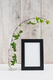 Picture frame with black border and vase with ivy on white desk