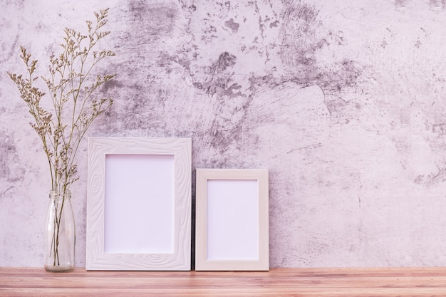 Picture frame with flowers on wall and wooden table.