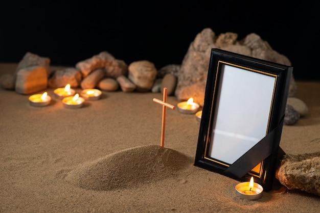 石のキャンドルと暗い表面に小さな墓と額縁