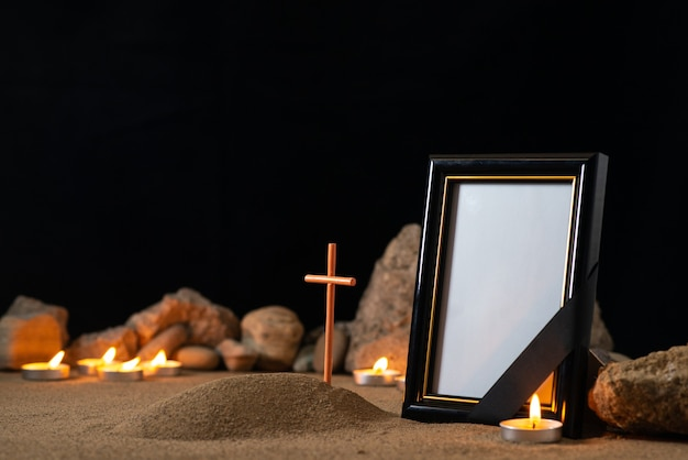 Picture frame with stones candles and little grave on dark surface