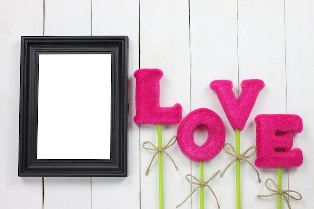 Picture frames and love letters on wooden floor.