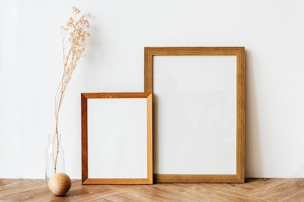 Picture frames on a wooden sideboard table with dried flowers