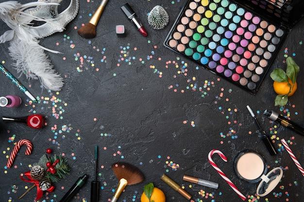 メイクアップアーティスト、マンダリン、クリスマスモミ、中央にテキストの場所がある黒いテーブルのサトウキビのアクセサリーの上からの写真