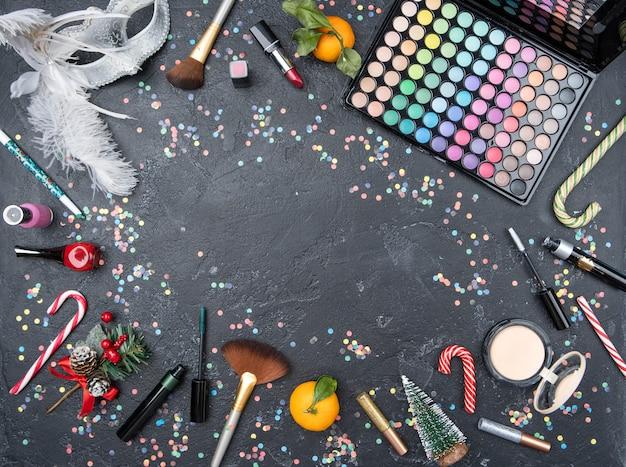 メイクアップアーティスト、マンダリン、クリスマスモミ、黒いテーブルのサトウキビのアクセサリーの上からの写真