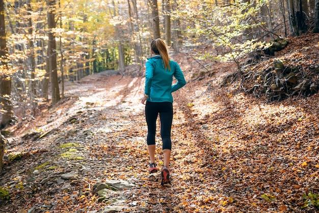 Фотография со спины спортивной молодой женщины, бегущей в парке осенним утром.