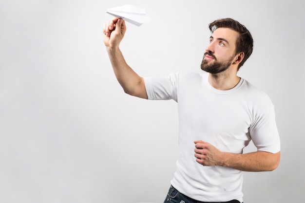A picture from a different angle where the man in white shirt is ready to lauch his paper airplane. he can do it any second. isolated on white wall.