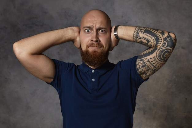 Picture of frustrated emotional european man with shaved head and fuzzy beard stylish hair grimacing, going to cry because of loud noise or argument with his girlfriend, covering his ears with hands