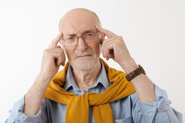 Picture of frustrated european bearded pensioner pressing temples with fingers having mournful painful facial expression, going to cry, feeling stressed because of headache or financial problems