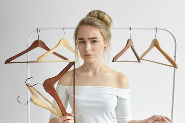 Picture of frustrated young caucasian woman in white top with open shoulders posing in bedroom with empty hangers in hands and rail behind her, perplexed after husband left her, taking all his clothes