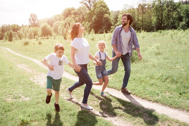 A picture of full family walking and jumping together on the road. they are going through green meadow. they are laughing.