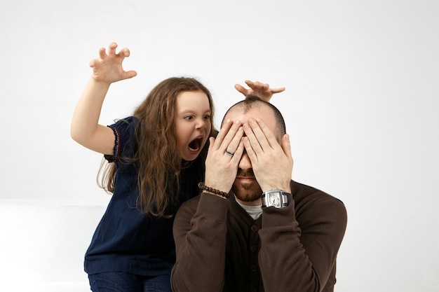 Picture of funny european female kid dressed casually opening mouth widely, shouting, frightening her young stylish dad who is sitting and covering eyes, feeling scared and terrified