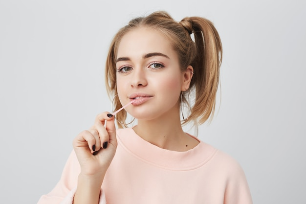 Picture of funny, playful, fashionable female student with appealing dark eyes, looking , enjoying free time at home after lectures at university. cute girl stretching chewing gum.