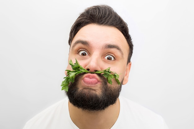 Picture of funny young man standing and lookin. he makes funny faces. this time guy puts parsley between lips and nose.