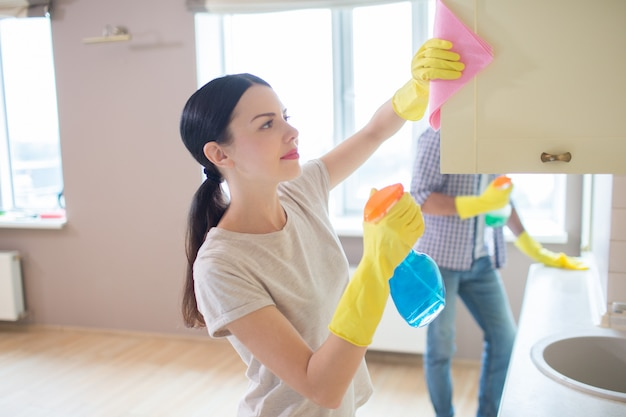A picture of girl cleaning the surface of wardrobe with pink rag. her husband is standing and doing the same thing forward. people are concentrated.