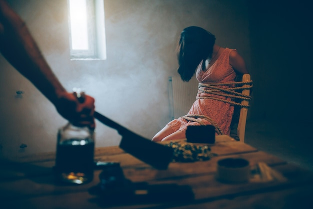 A picture of girl sitting on chair and tied with ropes. she is without consciousness. brunette girl is sitting near small window. room is dark. man's hand is holding big knife.